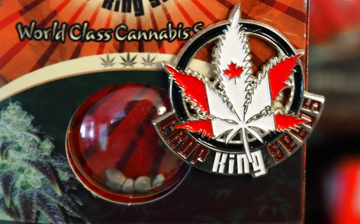 (AP Photo/Ted S. Warren). In this Sept. 24, 2018 photo, a pin promoting Crop King Seeds, with the colors and maple-leaf logo of the Canadian flag, is displayed on a package of marijuana seeds for sale at the Warmland Centre, a medical marijuana dispens...