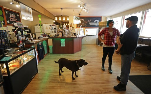 (AP Photo/Ted S. Warren). In this Sept. 24, 2018 photo, customer Seth McKay, right, talks with manager Ruby Bressan, at the Warmland Centre, a medical marijuana dispensary in Mill Bay, British Columbia, on Vancouver Island, as shop dog Delilah looks on...