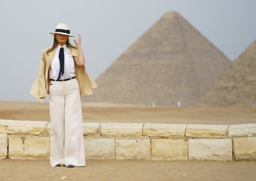 (AP Photo/Carolyn Kaster). First lady Melania Trump reaches for her hat as she pauses for media during a visit to the historical Giza Pyramids site near Cairo, Egypt on Saturday, Oct. 6, 2018. Trump is visiting Africa on her first big solo internationa...