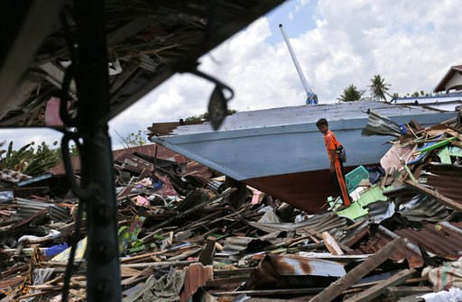 (AP Photo/Dita Alangkara). A young man stands near a boat swept ashore by the tsunami in Wani village on the outskirt of Palu, Central Sulawesi, Indonesia, Wednesday, Oct. 10, 2018. A 7.5 magnitude earthquake rocked Central Sulawesi province on Sept. 2...