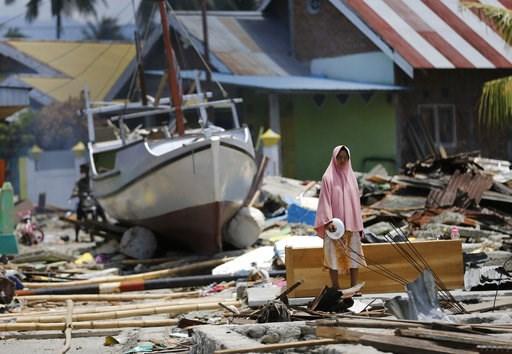 (AP Foto/Dita Alangkara). Una mujer de pie entre los escombros de viviendas cerca de un barco arrastrado tierra adentro por un tsunami, en la localidad de Wani, a las afueras de la ciudad de Palu, en el centro de la isla indonesia de Célebes, el 10 de ...