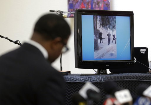 (AP Photo/Jeff Chiu, File). FILE - In this Jan. 18, 2016 file photo, attorney Adante D. Pointer, left, speaks at a news conference in San Francisco, as a video is displayed of the San Francisco police shooting of Mario Woods who police say appeared to ...