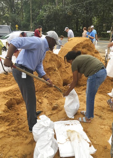 (AP Photo/Gary Fineout). Tallahassee Mayor and Democratic gubernatorial candidate, Andrew Gillum, left, helps Eboni Sipling fill up sandbags in Tallahassee, Fla., Monday, Oct. 8, 2018. Residents in Florida's Panhandle and Big Bend are getting ready for...
