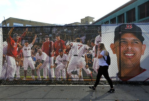 (AP Photo/Elise Amendola). A woman walks by large photo scrims hanging outside Fenway Park showing Boston Red Sox players and manager Alex Cora, Wednesday, Oct. 10, 2018, in Boston. Game 1 of the baseball American League Championship Series between the...