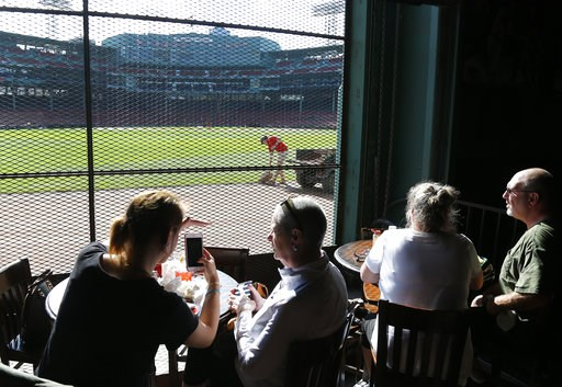(AP Photo/Elise Amendola). Patrons inside the Bleacher Bar enjoy the view of Fenway Park, in Boston, Wednesday, Oct. 10, 2018, as grounds crew get the field ready for Game 1 of the baseball American League Championship Series between the Boston Red Sox...