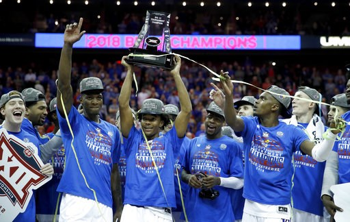 (AP Photo/Charlie Riedel, File). FILE - In this March 10, 2018, file photo, Kansas players celebrate after winning the Big 12 NCAA college basketball championship game against West Virginia, in Kansas City, Mo. With a bunch of transfers becoming eligib...
