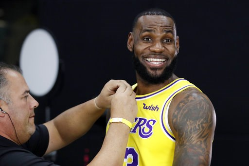 (AP Photo/Marcio Jose Sanchez, File). FILE - In this Monday, Sept. 24, 2018, file photo, Los Angeles Lakers' LeBron James smiles as a microphone is placed on his chest during media day at the NBA basketball team's practice facility in El Segundo, Calif...