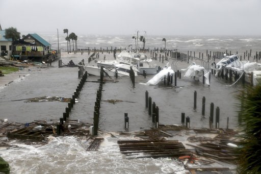 (Douglas R. Clifford/Tampa Bay Times via AP). Storm Surge retreats from inland areas, foreground, where boats lay sunk and damaged at the Port St. Joe Marina, Wednesday, Oct. 10, 2018 in Port St. Joe, Fla. Supercharged by abnormally warm waters in the ...