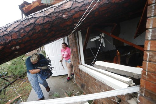 (AP Photo/Gerald Herbert). Megan Williams, left, and roommate Kaylee O'Brian take belongings from their destroyed home after several trees fell on the house during Hurricane Michael in Panama City, Fla., Wednesday, Oct. 10, 2018.