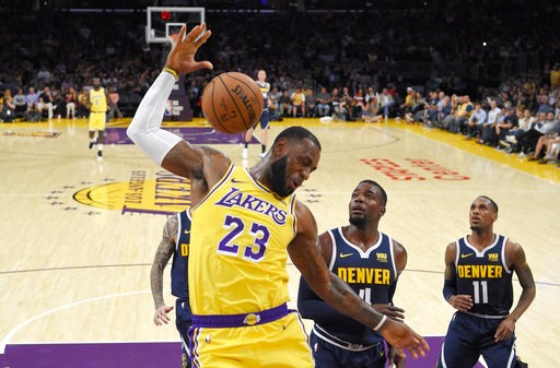 (AP Photo/Mark J. Terrill, File). FILE - In this Tuesday, Oct. 2, 2018, file photo, Los Angeles Lakers forward LeBron James, left, dunks as Denver Nuggets forward Paul Millsap, center, and guard Monte Morris watch during the first half of an NBA basket...
