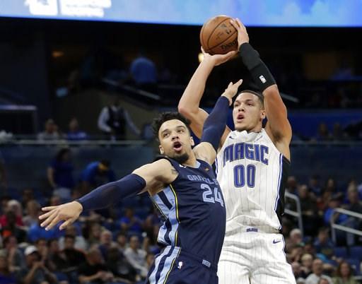 (AP Photo/John Raoux). Memphis Grizzlies' Dillon Brooks watches as Orlando Magic's Aaron Gordon (00) launches a 3-point shot during the second half of an NBA preseason basketball game Wednesday, Oct. 10, 2018, in Orlando, Fla.