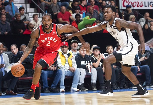 (Graham Hughes/The Canadian Press via AP). Toronto Raptors' Kawhi Leonard (2) drives to the basket as Brooklyn Nets' Treveon Graham defends during the first half of an NBA basketball preseason game Wednesday, Oct, 10, 2018, in Montreal.