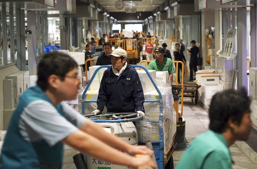 (AP Photo/Eugene Hoshiko). Workers carry merchandise on the first official opening day at the newly opened Toyosu Market, new site of Tokyo's fish market, in Tokyo Thursday, Oct. 11, 2018. Thursday was the first day of business at the new facility on T...