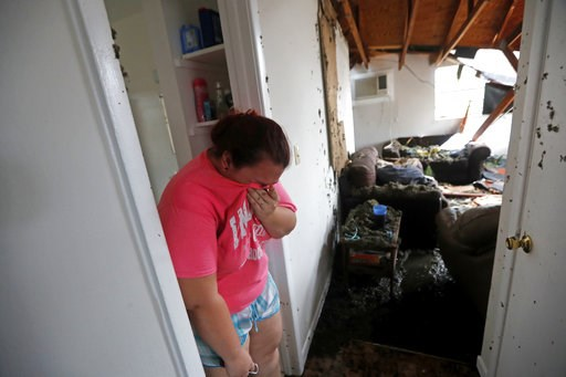 (AP Photo/Gerald Herbert). Kaylee O'Brian weeps inside her home after several trees fell on it during Hurricane Michael in Panama City, Fla., Wednesday, Oct. 10, 2018.