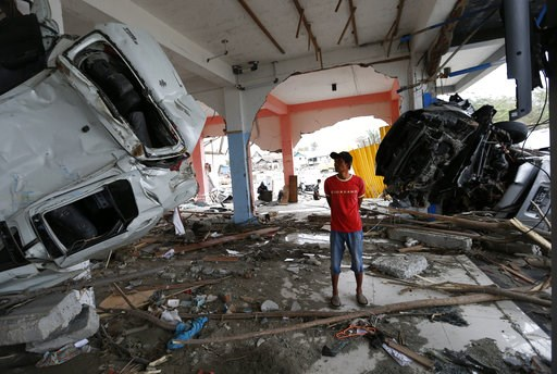 (AP Photo/Dita Alangkara). A man inspects the wreckage of vehicles inside a building at the tsunami-ravaged area in Palu, Central Sulawesi, Indonesia, Thursday, Oct. 11, 2018. A 7.5 magnitude earthquake rocked Central Sulawesi province on Sept. 28, tri...