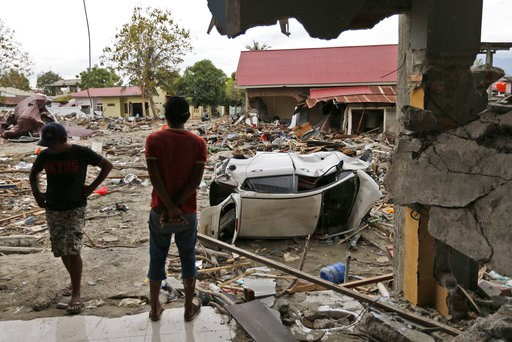(AP Photo/Dita Alangkara). Men view the damage at a tsunami-ravaged area in Palu, Central Sulawesi, Indonesia, Thursday, Oct. 11, 2018. A 7.5 magnitude earthquake rocked Central Sulawesi province on Sept. 28, triggering a tsunami and mudslides that kil...