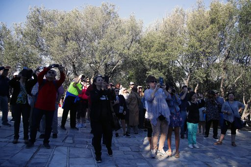 (AP Photo/Thanassis Stavrakis). Tourists take photographs outside the closed Acropolis ancient site in Athens, Thursday, Oct. 11, 2018 during a 24-hour strike called by a Greek union representing staff at the country's ancient site. The union accused t...