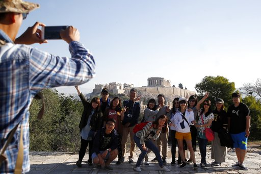 (AP Photo/Thanassis Stavrakis). Tourists from Taiwan take photographs with the closed Acropolis ancient site in the background in Athens, Thursday, Oct. 11, 2018 during a 24-hour strike called by a Greek union representing staff at the country's ancien...