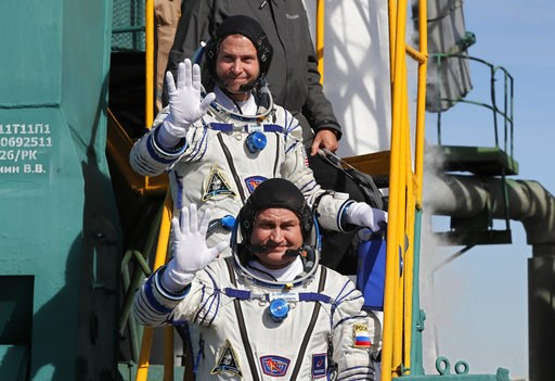 (Yuri Kochetkov, Pool Photo via AP). U.S. astronaut Nick Hague, right, and Russian cosmonaut Alexey Ovchinin, crew members of the mission to the International Space Station wave as they board the rocket prior to the launch of Soyuz-FG rocket at the Rus...