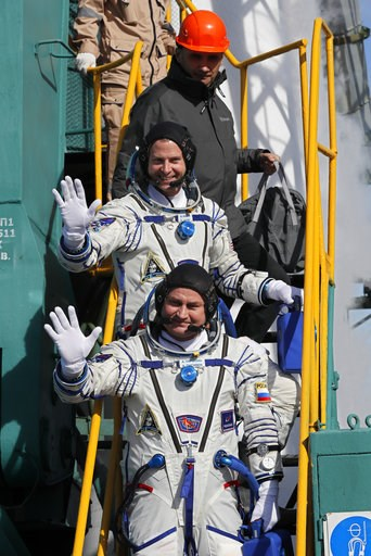 (Yuri Kochetkov, Pool Photo via AP). U.S. astronaut Nick Hague, right, and Russian cosmonaut Alexey Ovchinin, crew members of the mission to the International Space Station, ISS, wave as they board to the rocket prior the launch of Soyuz-FG rocket at t...