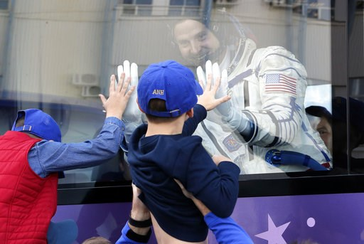 (AP Photo/Dmitri Lovetsky, Pool). U.S. astronaut Nick Hague, member of the main crew to the International Space Station (ISS), waves to his sons from a bus prior to the launch of Soyuz-FG rocket at the Russian leased Baikonur cosmodrome, Kazakhstan, Th...