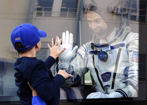 (AP Photo/Dmitri Lovetsky, Pool). U.S. astronaut Nick Hague, member of the main crew to the International Space Station (ISS), waves to his son from a bus prior to the launch of Soyuz-FG rocket at the Russian leased Baikonur cosmodrome, Kazakhstan, Thu...