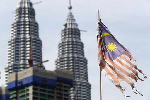 (AP Photo/Vincent Thian, File). FILE - In this April 10, 2018, a battered Malaysian national flag flies in front of the Petronas Towers in Kuala Lumpur, Malaysia. Malaysia's government says it will abolish the death penalty and halt all executions, in ...