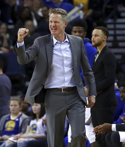 (AP Photo/Ben Margot, File). FILE - In this March 14, 2018, file photo, Golden State Warriors coach Steve Kerr gestures in front of Stephen Curry during the second half of the team's NBA basketball game against the Los Angeles Lakers in Oakland, Calif....