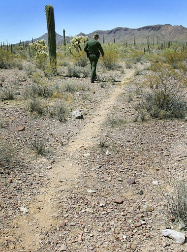 (AP Photo/Matt York). FILE - In this May 24, 2006, file photo, U.S. Border Patrol Senior Agent Sean King patrols a trail in Organ Pipe Cactus National Monument near Lukeville, Ariz. Smugglers in recent weeks have been abandoning large groups of Guatema...