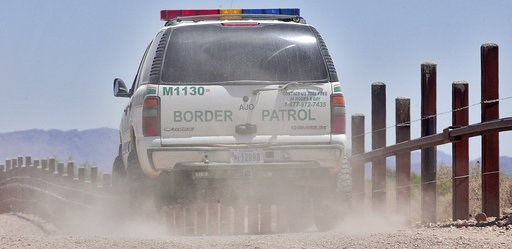(AP Photo/Matt York). FILE - In this May 26, 2006 file photo, a U.S. Border Patrol agent patrols the international border separating Sonoyta, Mexico, right of fence, and Lukeville, Ariz., in Organ Pipe Cactus National Monument. Smugglers in recent week...