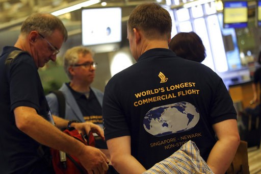 (AP Photo/Wong Maye-E). Passengers wearing self designed t-shirts which celebrate their trip on Singapore Airline's inaugural non-stop flight to New York, wait at the check-in counter on Thursday, Oct. 11, 2018, in Singapore. The world's longest flight...