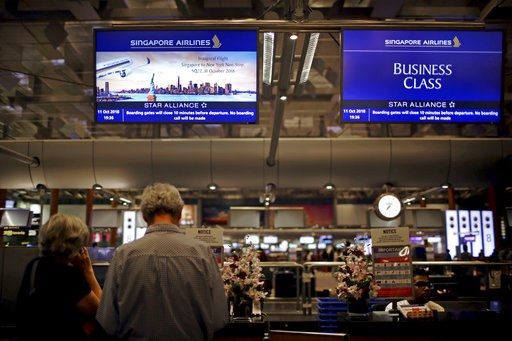 (AP Photo/Wong Maye-E). Passengers traveling on Singapore Airlines flights wait at check-in counters where advertisements for the airline's inaugural non-stop flight from Singapore to New York is flashed on screens on Thursday, Oct. 11, 2018, in Singap...
