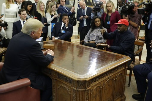 (AP Photo/Evan Vucci). Rapper Kanye West speaks to President Donald Trump and others in the Oval Office of the White House, Thursday, Oct. 11, 2018, in Washington.