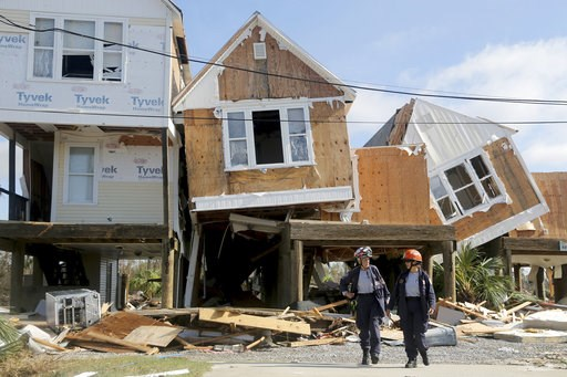 (Douglas R. Clifford/Tampa Bay Times via AP). Emergency workers Dr. Patricia Cantrell, left, and Ana Kaufmann, with the South Florida Search and Rescue Task Force 2, survey damage at the western edge of town in Mexico Beach, Fla., after Hurricane Micha...