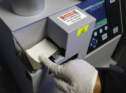 (AP Photo/Rich Pedroncelli, file). FILE - In this May 20, 2015 file photo, Correctional Officer M. Jones, puts a test sample on an airport-style ion spectrometer that tests for illegal narcotics at Vacaville State Prison in Vacaville, Calif. The federa...
