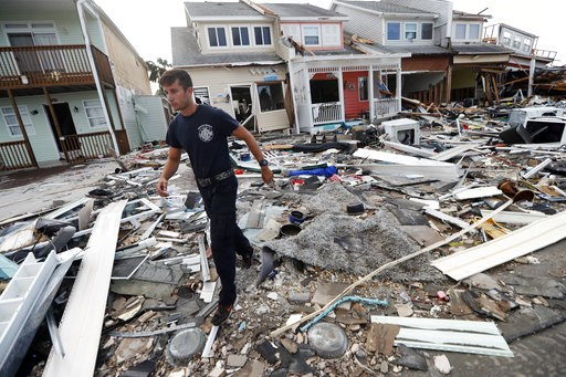 (AP Photo/Gerald Herbert). Firefighter Austin Schlarb performs a door to door search in the aftermath of Hurricane Michael in Mexico Beach, Fla., Thursday, Oct. 11, 2018.