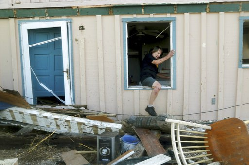 (Douglas R. Clifford/Tampa Bay Times via AP). James Murphy emerges from what remains of his home on Thursday, Oct. 11, 2018, on a coastal stretch of Port St. Joe, Fla. The home was severely damaged by Hurricane Michael's violent storm surge and wind as...