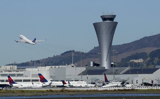 (AP Photo/Jeff Chiu, File). FILE - In this Oct. 24, 2107 file photo, the air traffic control tower is in sight as a plane takes off from San Francisco International Airport in San Francisco. Aviation-safety officials say a close call last year highligh...