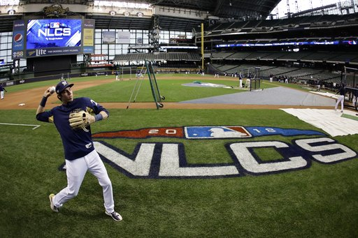 (AP Photo/Matt Slocum). Milwaukee Brewers' Christian Yelich warms up for practice for Game 1 of the National League Championship Series baseball game Los Angeles Dodgers Thursday, Oct. 11, 2018, in Milwaukee.