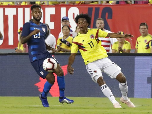 (AP Photo/John Raoux). Colombia's Juan Cuadrado (11) moves the ball away from Unites States' Kellyn Acosta, left, during the first half of an international friendly soccer match Thursday, Oct. 11, 2018, in Tampa, Fla.