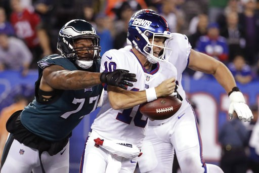 (AP Photo/Julio Cortez). Philadelphia Eagles defensive end Michael Bennett (77) strips the ball from New York Giants quarterback Eli Manning during the first half of an NFL football game Thursday, Oct. 11, 2018, in East Rutherford, N.J.