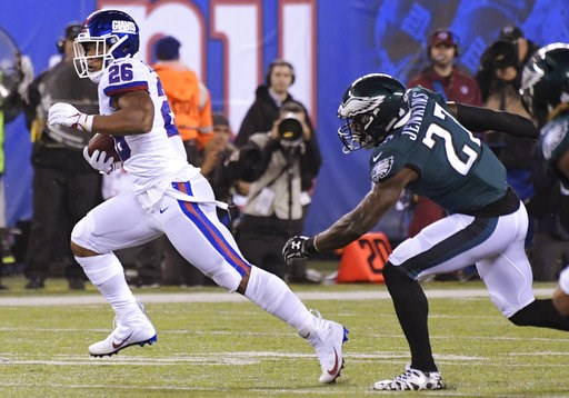 (AP Photo/Bill Kostroun). New York Giants running back Saquon Barkley (26) runs away from Philadelphia Eagles' Malcolm Jenkins (27) and Jalen Mills (31) during the first half of an NFL football game Thursday, Oct. 11, 2018, in East Rutherford, N.J.