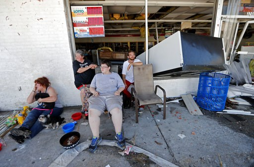 (AP Photo/Gerald Herbert). Dawn Vickers, left, her mother Patsy Vickers, son Ryder Vickers, and friend Robert Brock, right, who rode out Hurricane Michael in their now-destroyed home, sit in front of a damaged convenience store with nowhere to go, in M...