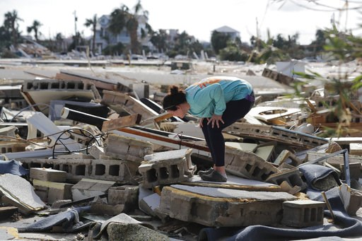 (AP Photo/Gerald Herbert). Mishelle McPherson looks for her friend in the rubble of her home, since she knows she stayed behind in the home during Hurricane Michael, in Mexico Beach, Fla., Thursday, Oct. 11, 2018.