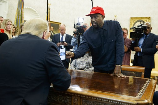 (AP Photo/Evan Vucci). Rapper Kanye West shows President Donald Trump a photograph of a hydrogen plane during a meeting in the Oval Office of the White House, Thursday, Oct. 11, 2018, in Washington.