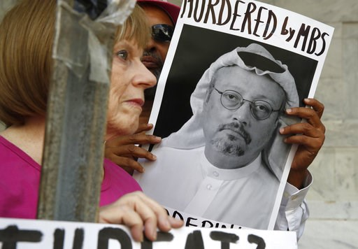 (AP Photo/Jacquelyn Martin, File ). FILE - In this Oct. 10, 2018, file photo, people hold signs during a protest at the Embassy of Saudi Arabia about the disappearance of Saudi journalist Jamal Khashoggi, in Washington. The Trump administration's ongoi...