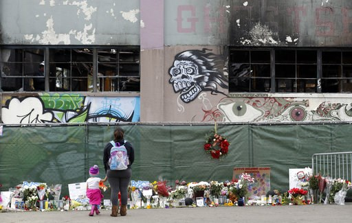 (AP Photo/Marcio Jose Sanchez, File). FILE - In this Dec. 13, 2016, file photo, flowers, pictures, signs and candles, are placed at the scene of a warehouse fire in Oakland, Calif. A judge will hear a motion asking the court to uphold a plea bargain th...