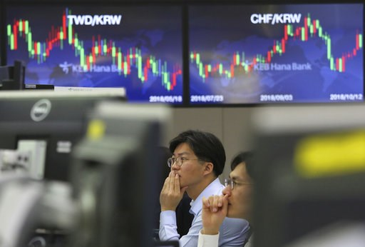 (AP Photo/Ahn Young-joon). Currency traders watch monitors at the foreign exchange dealing room of the KEB Hana Bank headquarters in Seoul, South Korea, Friday, Oct. 12, 2018. Asian stocks were mixed on Friday as better-than-expected Chinese trade data...