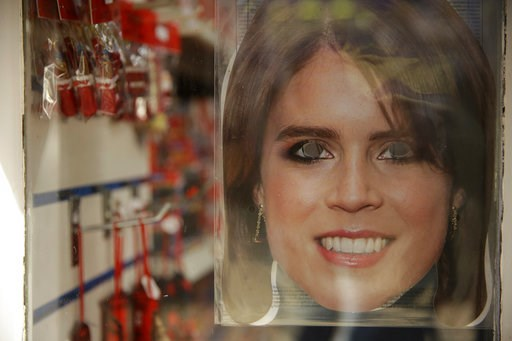 (AP Photo/Matt Dunham). A Princess Eugenie mask is displayed for sale in the window of a souvenir shop ahead of the wedding of Britain's Princess Eugenie in Windsor, England, Wednesday, Oct. 10, 2018. The 28-year-old granddaughter of Queen Elizabeth II...