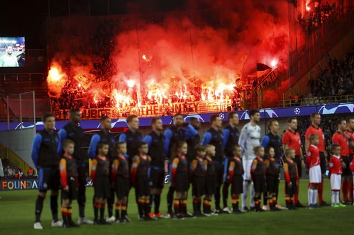 (AP Photo/Francisco Seco). In this photo taken on Tuesday, Sept. 18, 2018 Dortmund fans set off flares as Club Brugge players stand on the pitch prior their Champions League group A soccer match with Dortmund at the Jan Breydel Stadium in Bruges. Belgi...